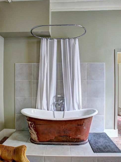 Weißer Duschvorhang hinter brauner Badewanne