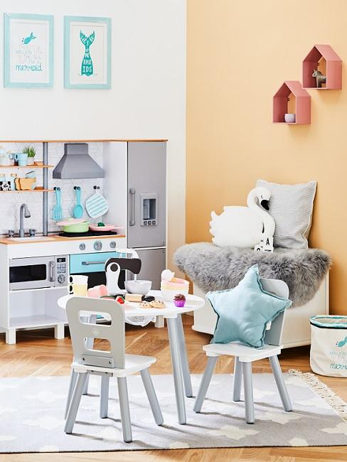 Apricotfarbene Wand im Kinderzimer mit Tisch, Stühlen und Spielzeug