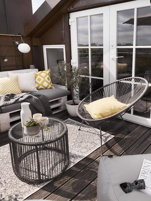 Schöner Balkon im monochromen Look mit gelben Kissen
