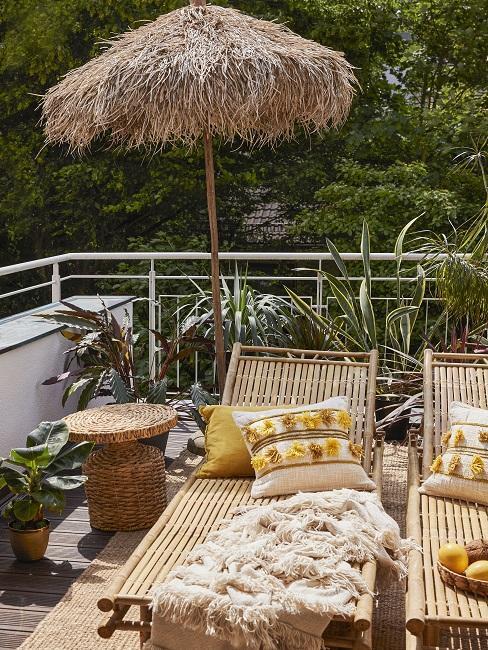 Schöner Balkon im Tropical Style mit Sonnenliegen, Sonnenschirm, gelben Dekokissen und Beistelltisch aus Bast