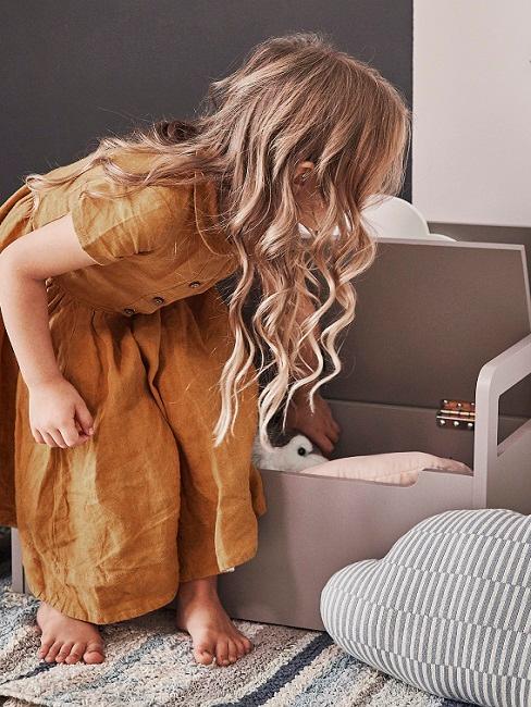 Mädchen räumt Spielzeug im Kinderzimmer in eine Kiste