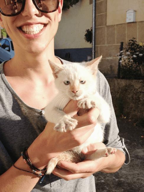 chico con un gato recien nacido en sus manos