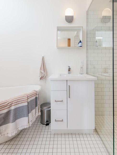 Cuarto de baño en tonos blancos con azulejos blancos en el suelo