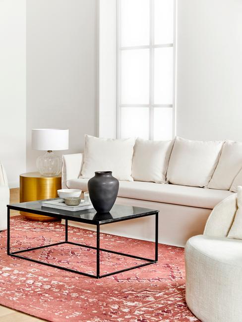 Sofá Mila en un salón moderno con alfombra persa y mesa baja de acero negra