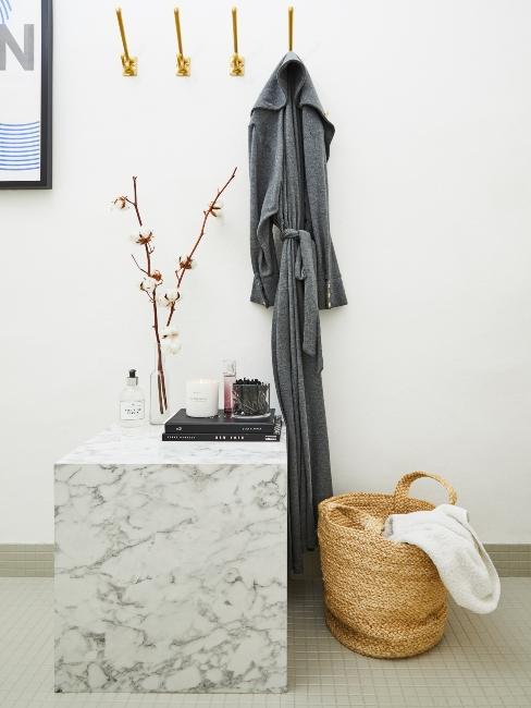 Peignoir sur crochet doré et cube en marbre dans salle de bain avec panier en osier