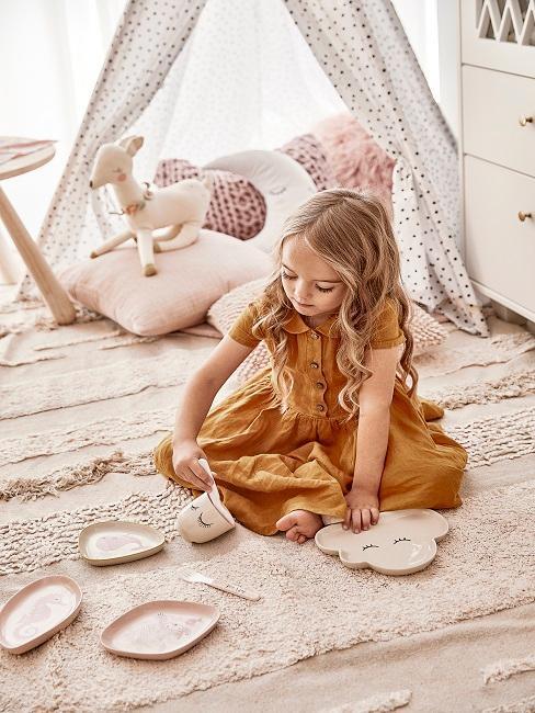 petite fille assise sur un tapis clair dans sa chambre couleurs pastel, tipi avec coussins et peluches