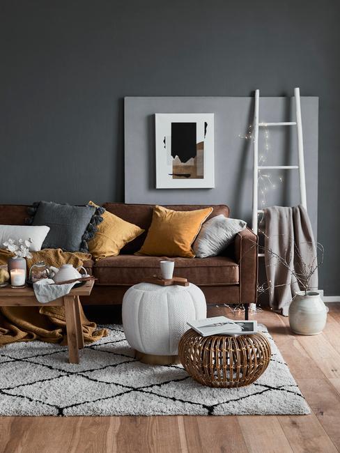 Salon avec un canapé en cuir marron sur lequel plusieurs coussins de couleurs sont placés. Le tout derrière une table basse en bois sur un tapis noir et blanc
