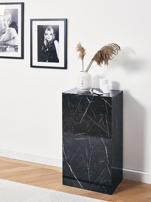 Couloir avec commode noire, tapis clair et photos encadrées sur les murs