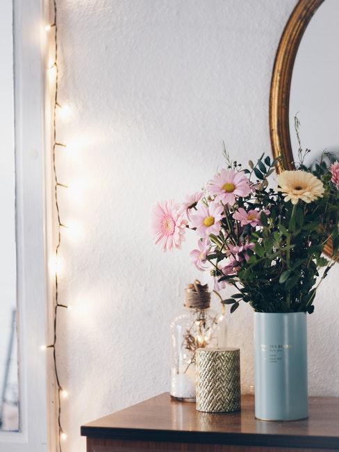 Miroir et bouquet de fleurs posé devant, une guirlande lumineuse décorant le mur