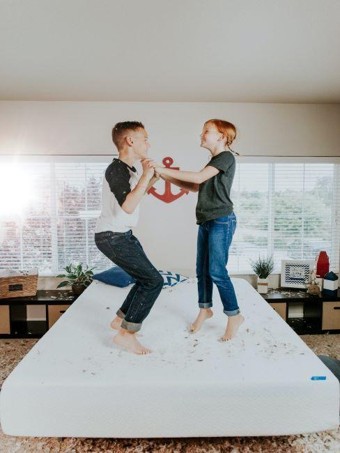 fille et garçon sautent sur un matelas