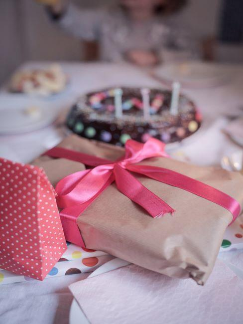 cadeau papier kraft avec ruban rose clair sur le premier plan, derriere un gateau d anniversaire