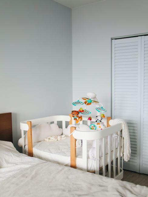 lit bebe blanc avec un mobile dans une chambre des parents