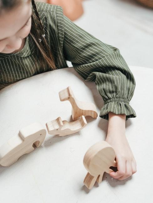 enfant joue avec des jouets en bois