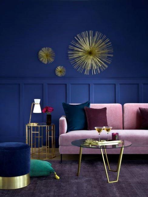 soggiorno con divano rosa e parete blu con boiserie