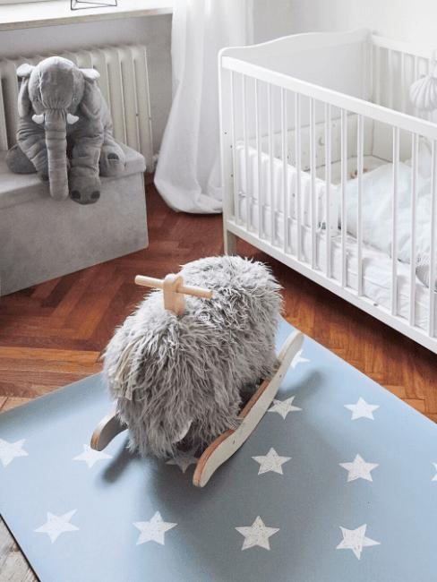 Complete babykamer in wit, blauw en grijs met babybedje, vloerkleed met sterren en schommeldier