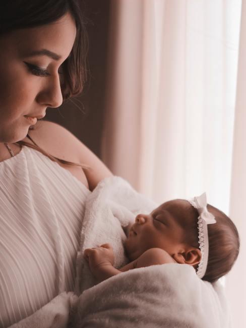 Moder houdt baby meisje vast met gordijnen op de achtergrond