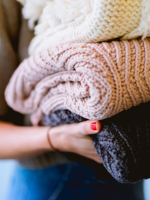 hand houdt 3 truien vast in grijs, roze en gebroken wit