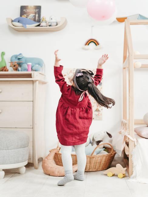 Meisje in rode jurk speelt in kinderkamer in natuurtinten