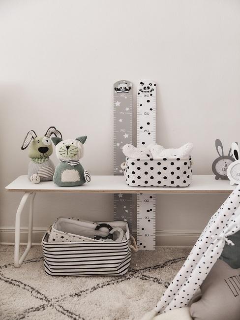 babykamer in grijs met tafel, groeimeter, pluchen speelgoed en mandje
