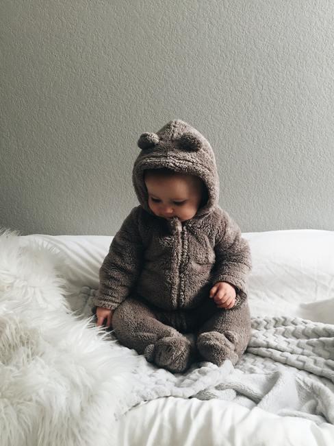 Baby in berenpakje op wit bed met grijze achtergrond - babykamer grijs