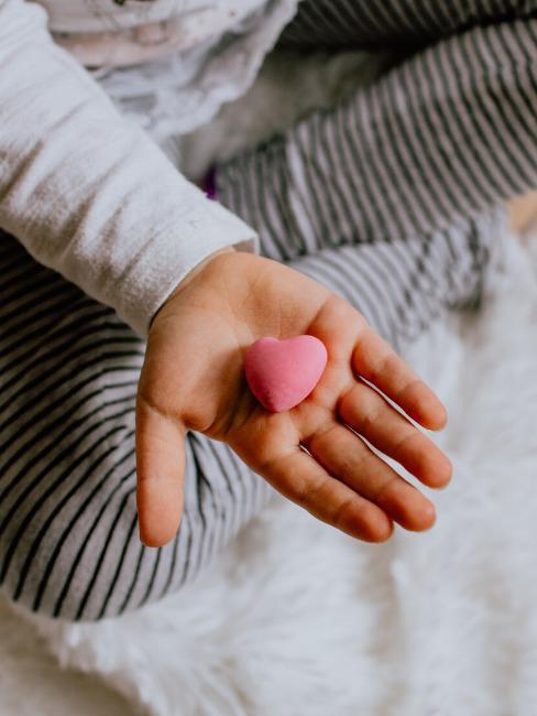 Een kind met een roze hart in haar hand