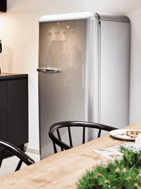 Zbliżenie na srebrną lodówkę oraz fragment drewnianego stołu i czarnych krzeseł
