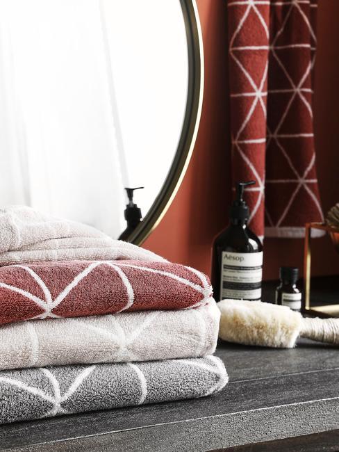 Ręczniki w geometryczne wzory na tle bordowej ściany i lustra w złotej ramie