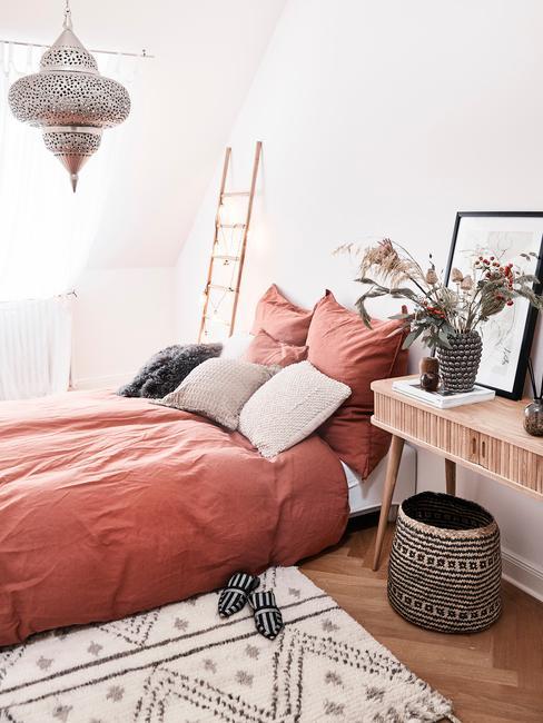Sypialnia w stylu orientalnym. Metalowy ozodobny żyrandol, wyplatane kosze i łóżko z pościelą w kolorze terakoty