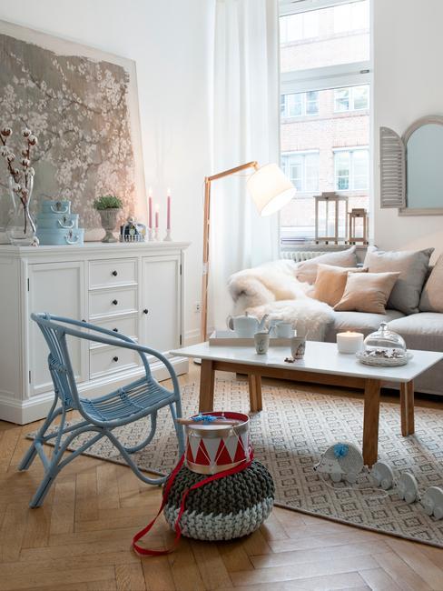 jasny salon z błękitnym krzesłem i jasna komodą