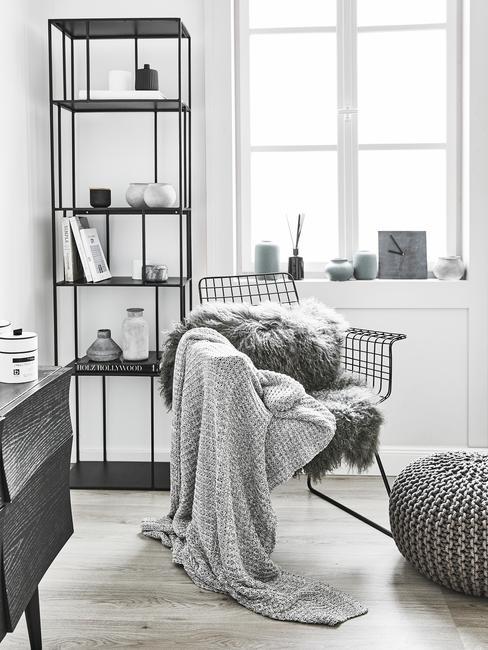 Biało-szary kącik do czytania. Regał z książkami a przy nim fotel z miękkim kocem