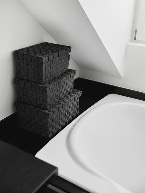 Zbliżenie na trzy pudełka do przechowywania w czarno - białej łazience