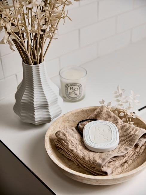 Umywalka w łazience z wazonem suszonych kwiatów, świeczką oraz drewnianą miseczką z mydłem