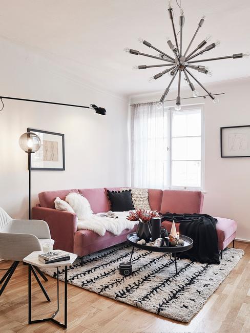 Różowa sofa narożna w małym salonie