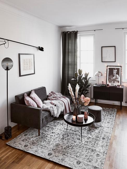 Mały salon z szarą sofą i dekoracjami na stoliku kawowym