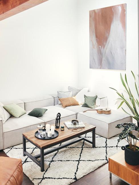 Salon z białymi ścianami, jasnobeżową narożną kanapą, stolikiem kawowym oraz rośliną