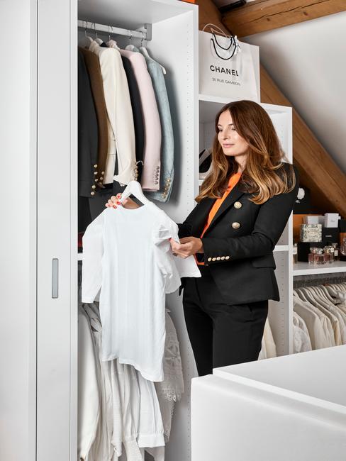 Kobieta stojąca przed białą szafą, z koszulką na wieszaku w ręku