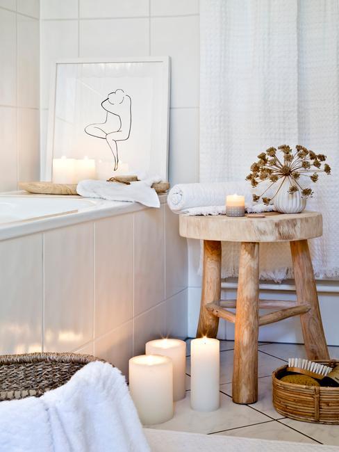 Fragment białej łazienki z wanną, drewnianym stołkiem oraz dekoracjami