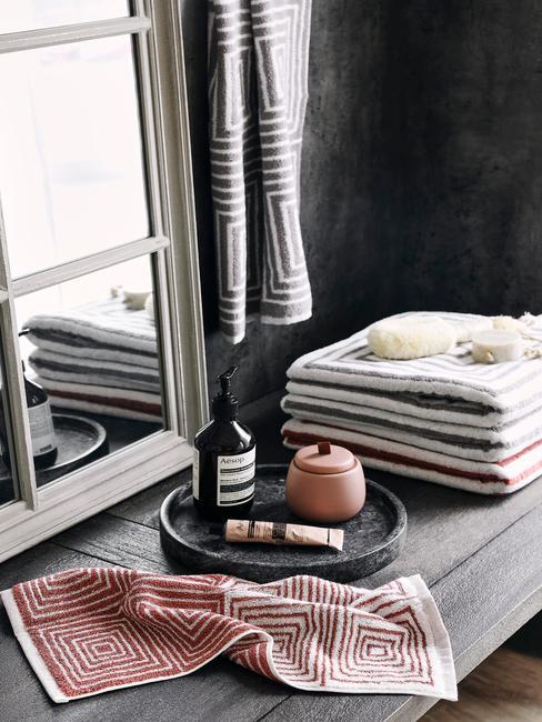 Fragment łazienki w stylu industrialnym z ręcznikami i dodatkami