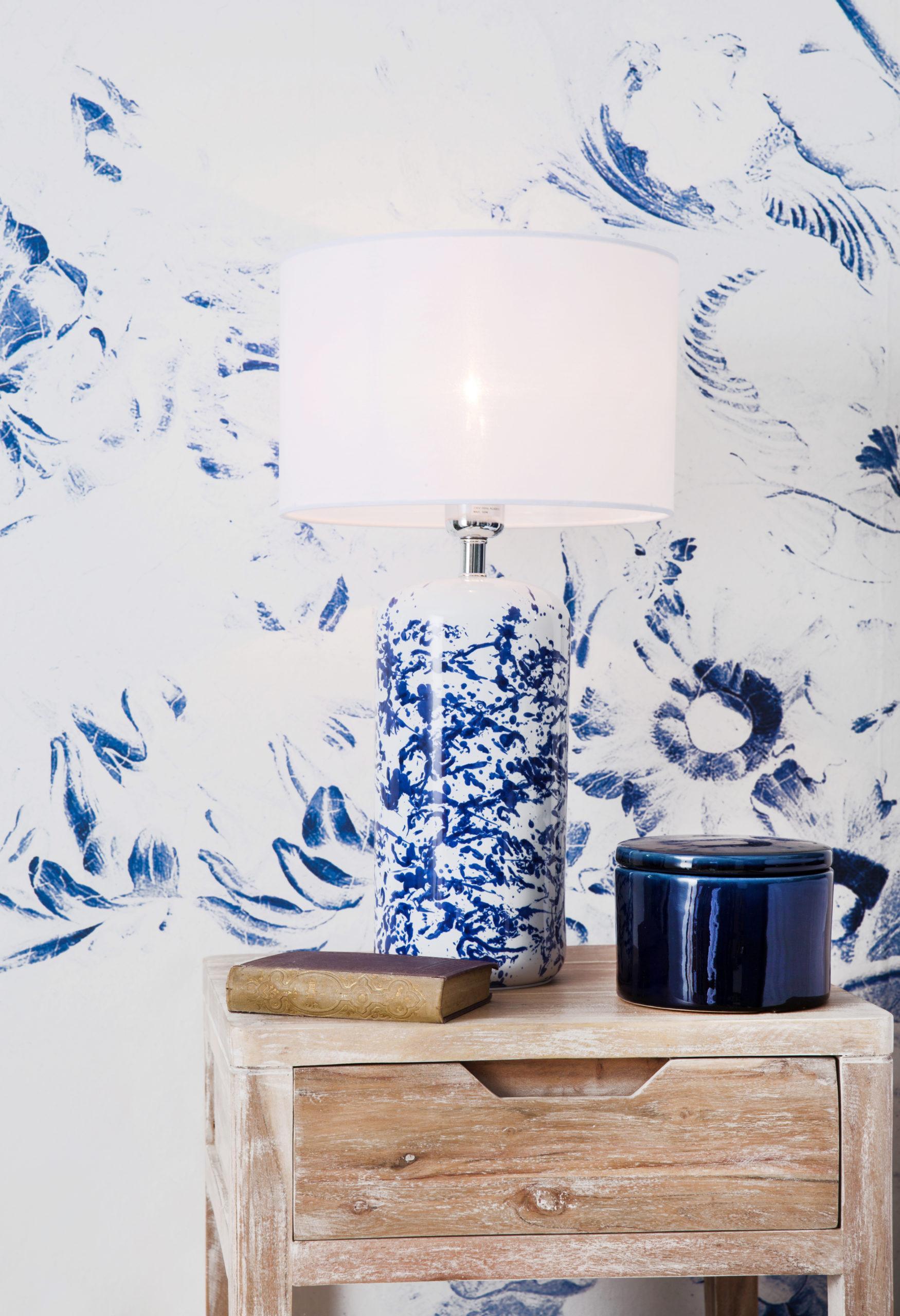 Biało-niebieska tapeta z drewnianym stolikiem nocnym oraz lampą