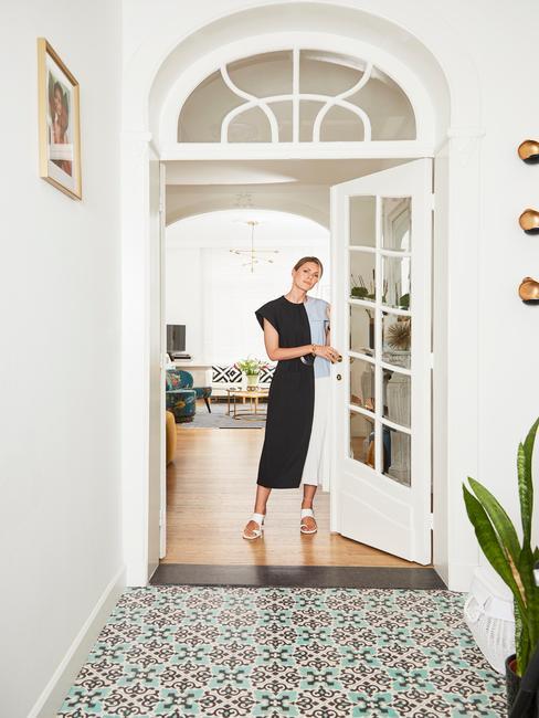 Kobieta stojąca przy białych drzwiach