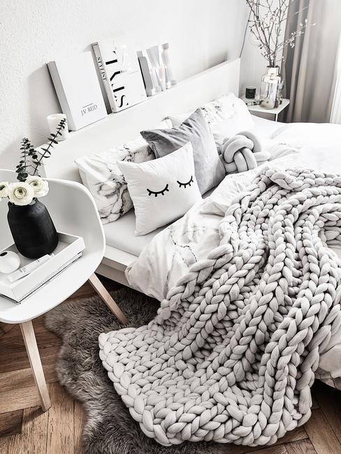 Biała sypialnia z szarycem kocem pledowym oraz poduszkami dekoracyjnymi