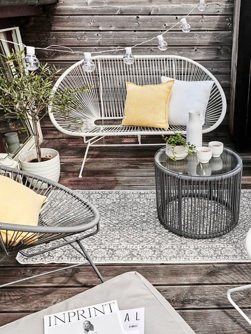 Drewniany balkon z meblami ogrodowymi oraz rośliną w białej doniczce