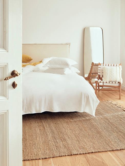 Biało-beżowa sypialnia z placionym dywanem, krzesłem, lustrem oraz łożkiem z białą pościelą