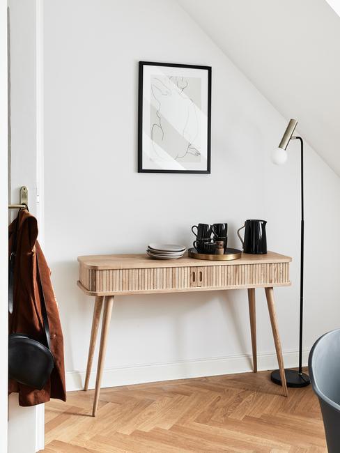 Fragment korytarza z drewnianym stolikiem, lampą oraz obrazkiem