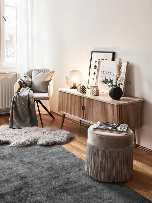 Skandynawski kącik w salonie w bloku z przytulnymi tekstyliami i dekoracjami