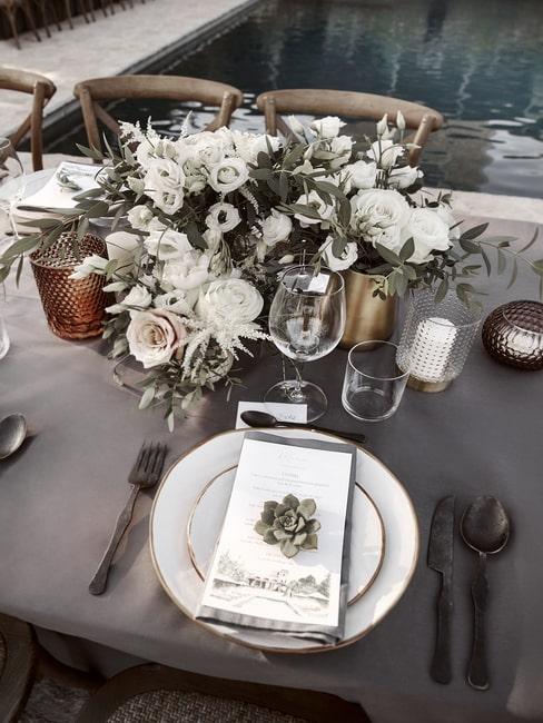 Nakryty stół weselny z kwiatowymi dekoracjami z eukaliptusem