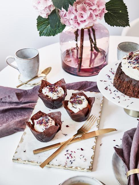 Zastawiony stół z wazonem, ciastem na paterze oraz babeczkami