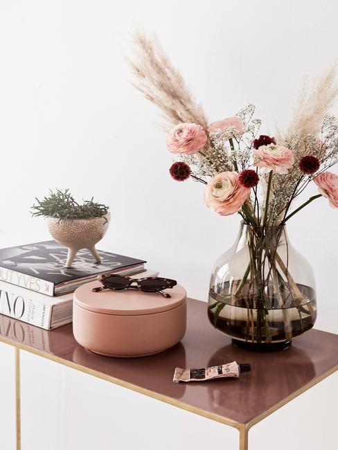 Szklany wazon z trawą pampasową i różowymi jaskrami