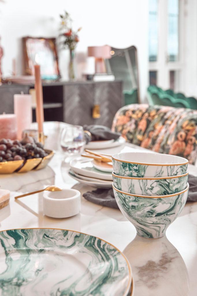 Zestaw zielono - białych naczyć na nakrytym, marmurowym stole w jadalni
