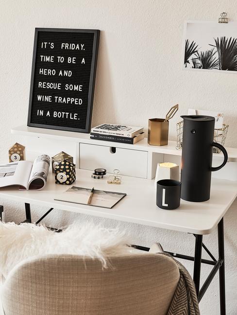 Biała przestrzeń w pomieszczeniu na domowe biuro z biurkiem oraz fotelem i czarnymi dekoracjami